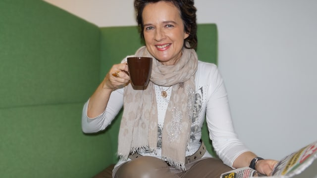 Monika Martin mit Kaffeetasse und Zeitung in der Hand.