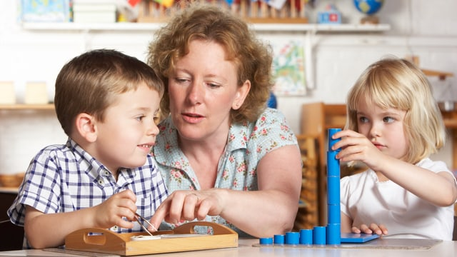 Frau hilft spielenden Kindern