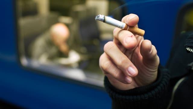 Hand hält Zigarette. Im Hintergrund ist ein Zug zu sehen.