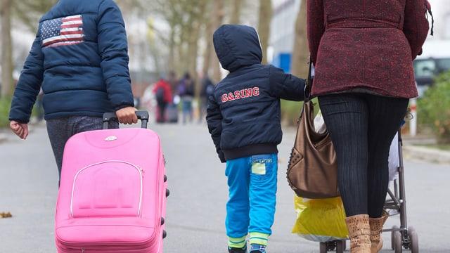 Eine Familie mit Kinderwagen und Reisekoffer