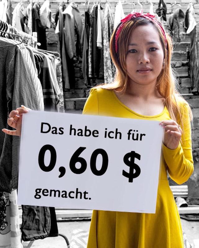 Eine Arbeiterin hält ein Schild mit der Aufschrift: Das habe ich für 0.60 Dollar gemacht.