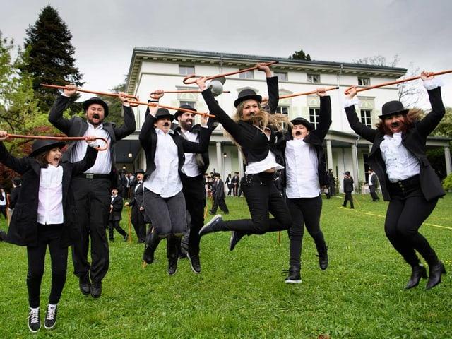 Erwachsene Chaplins hüpfen in die Luft.