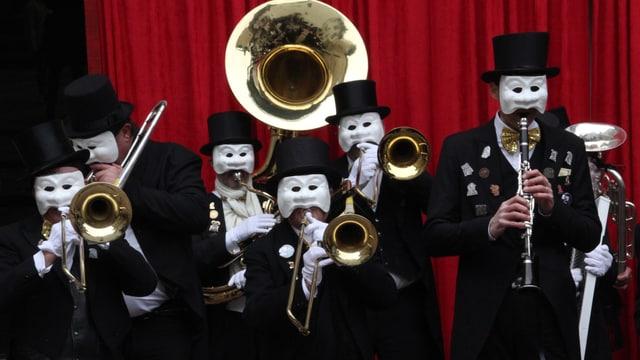 Sechs Mitglieder der Jeisi Migger machen Musik mit ihren Blasinstrumenten. Sie tragen weisse Larven, schwarze Zylinder und einen Frack.