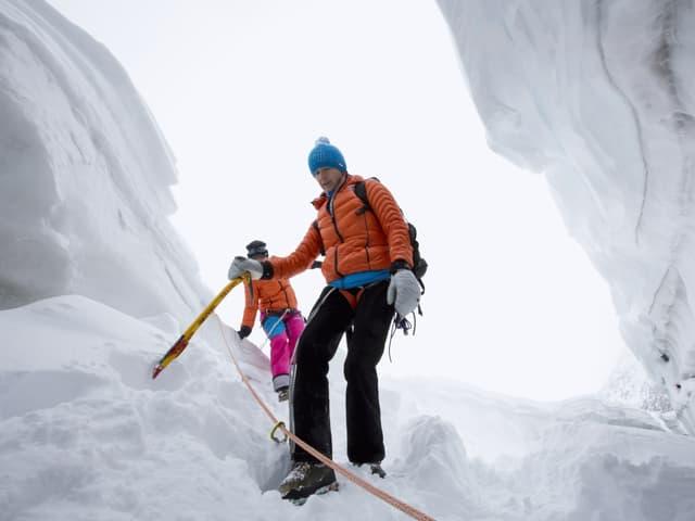 Die Glaziologien Andrea Fischer steigt am Seil gesichert in eine Gletschersplate.