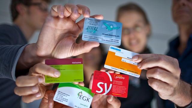 Mehrere Menschen strecken ihre Krankenversichertenkarte in die Kamera.