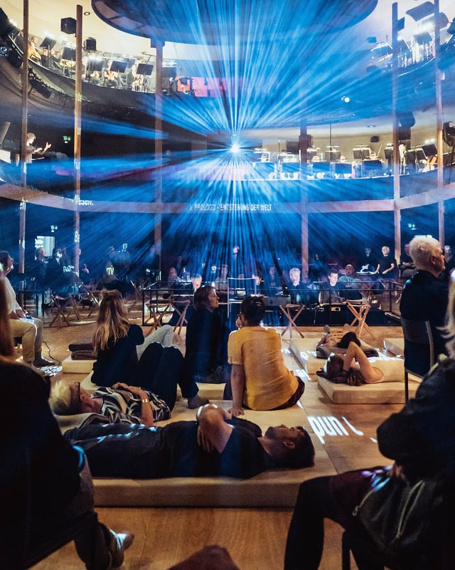 Menschen liegen und sitzen im Zuschauerraum eines Theaters.