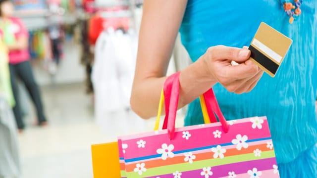 Eine Frau mit mehreren Einkaufstaschen am Arm, in der Hand eine Kreditkarte.