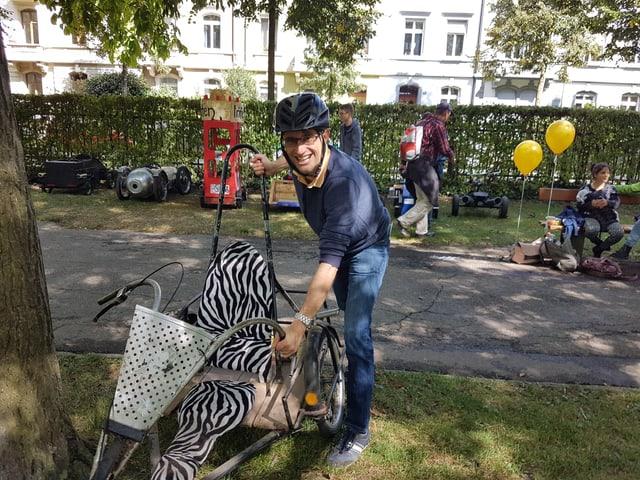 Regirungsrat Lukas Engelberger steht mit einem Helm auf dem Kopf bei einer Seifenkiste und lacht in die Kamera.