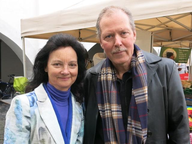 Paar vor Marktstand. Sie trägt einen farbigen Mantel und hat lange schwarze Haare. Er trägt einen karierten Schal.