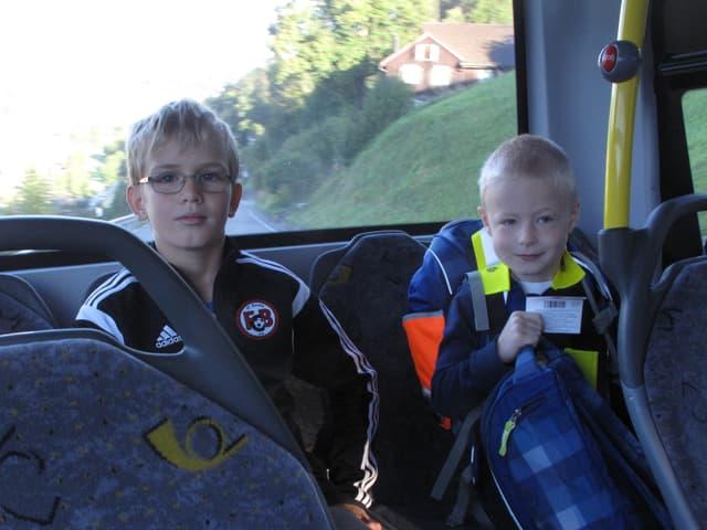 Die zwei Buben auf der Rückbank des kleinen Postautos