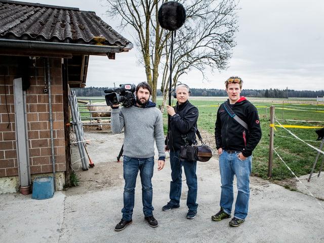 Kameramann, Tonoperator und Redaktor stehen nebeneinander auf dem Hof, neben einer Weide.