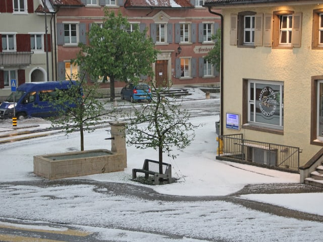 Ein Dorflplatz ist weis vor Hagel.