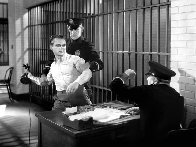 Cagney greift einen Polizisten an.