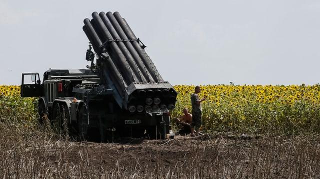 Ein ukrainischer Raketenwerfer in Stellung bei einem Sommenblumenfeld.