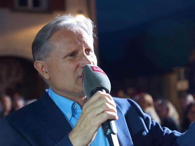 Ein Moderator mit Mikrofon.