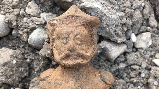 Eine kleine Tonfigur liegt zwischen Steinen.