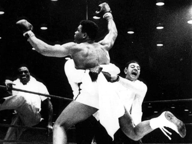 Ein Boxer jubelt mit gehobenen Armen nach einem gewonnen Boxkampf.