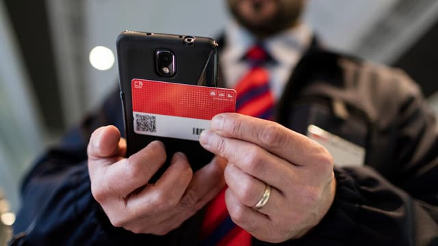 Ein Kontukteur mit Scanner und Swiss Pass