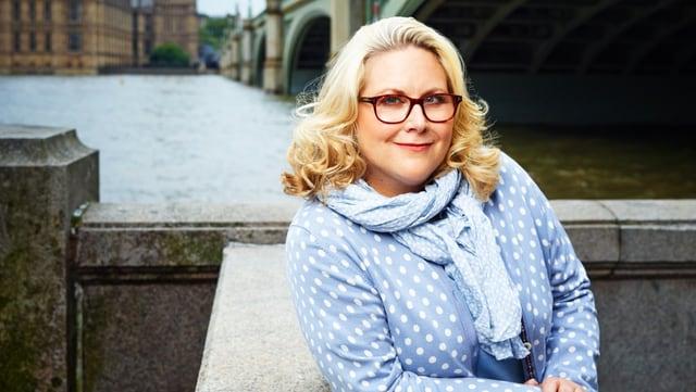 Kerstin Gier trägt einen hellblauen gepunkteten Pullover und steht an der Themse.