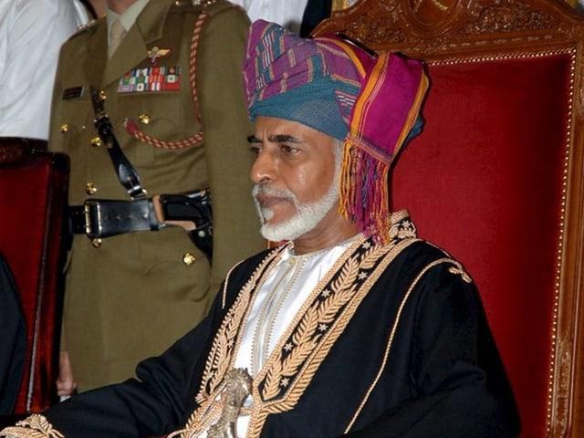 Sultan Kabus mit Turban auf einem roten Thron sitzend.