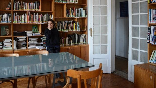Andrea Thal steht in einem alten Raum mit Parkett, Glastisch, grossem Buchregal und vielen Büchern.