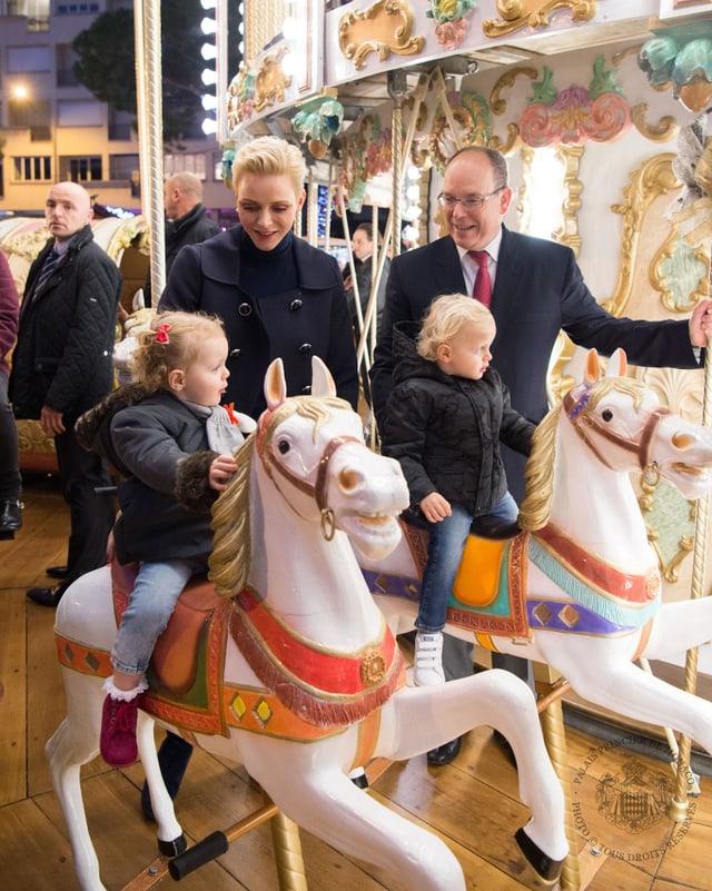 Fürst Albert und Fürstin Charlène mit ihren Zwillingen auf einem Kinderkarussel. Die Kinder sitzen auf kleinen Pferden.