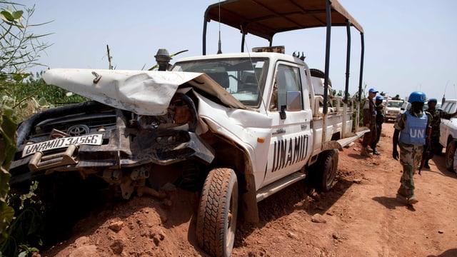 Soldat neben zerstörtem Fahrzeug