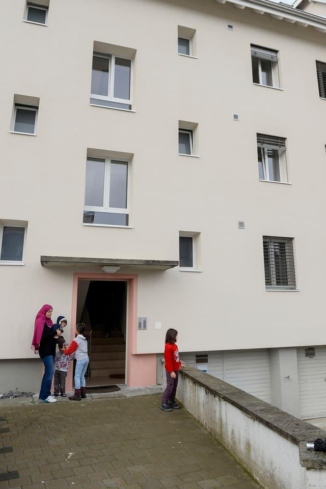 Frau mit Kopftuch und drei Kinder vor dem Eingang in einen Wohnblock