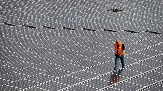 Mann geht über ein Dach aus Elementen einer Fotovoltaik-Anlage.
