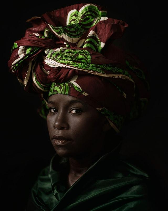 Porträt einer jungen schwarze Frau mit buntem Tuch auf dem Kopf.