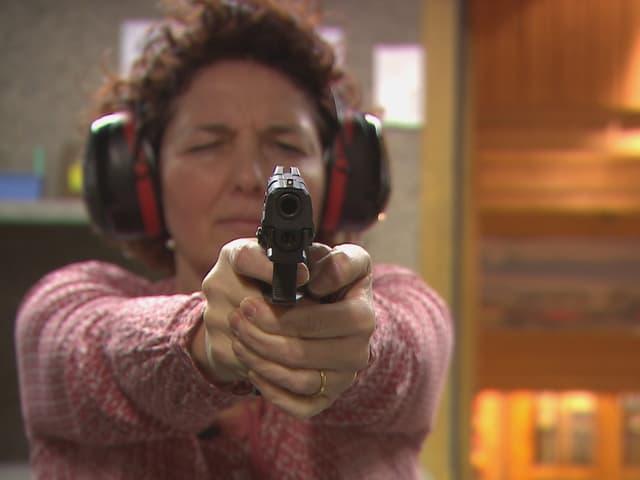 Eine Frau übt sich mit ihrer Waffe.