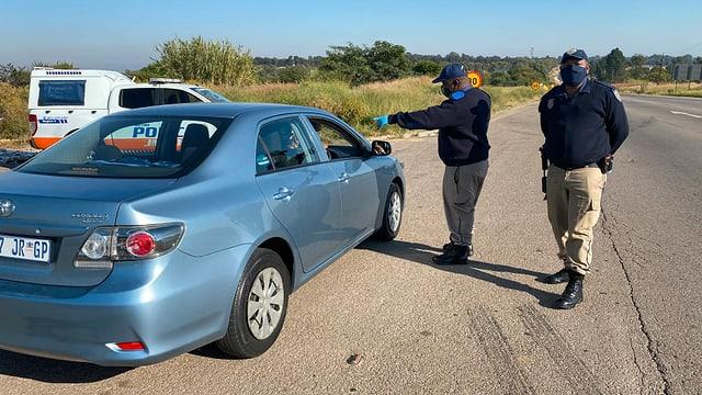 Zwei Polizisten kontrollieren ein blaues Auto.