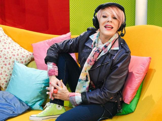 Birgit Steinegger als Aufnahmeleiterin auf einem Sofa sitzend