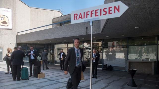 Raiffeisen-Wegweiser, dahinter Leute in Anzügen vor einem Bau.