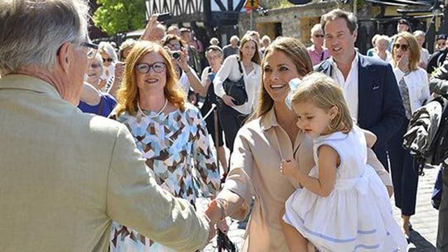 Prinzessin Madeleine hält Leonore in den Armen und begrüsst einen Mann.
