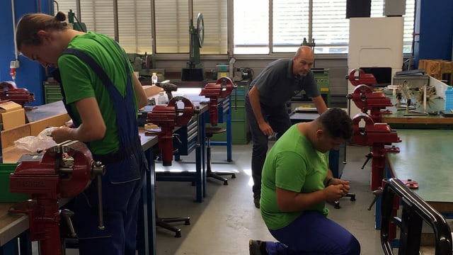 Blick in eine Werkstatt - zwei Lehrlinge sind am Arbeiten. Ein Lehrmeister schaut.