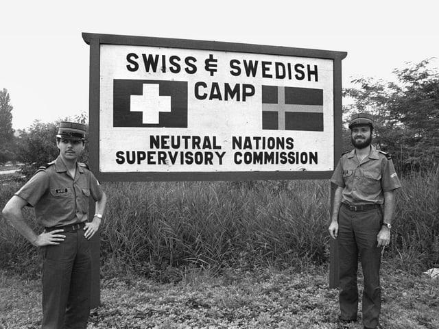 Soldaten vor einem Schild.