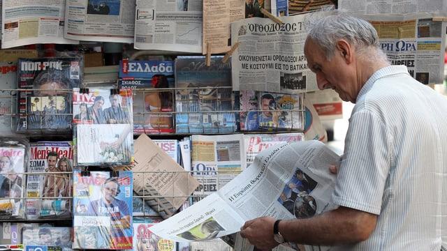 Ein Mann liest vor einem Kiosk eine Zeitung.