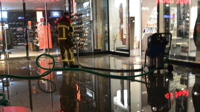 Feuerwehrmann mit Schlauch, am Boden Wasser