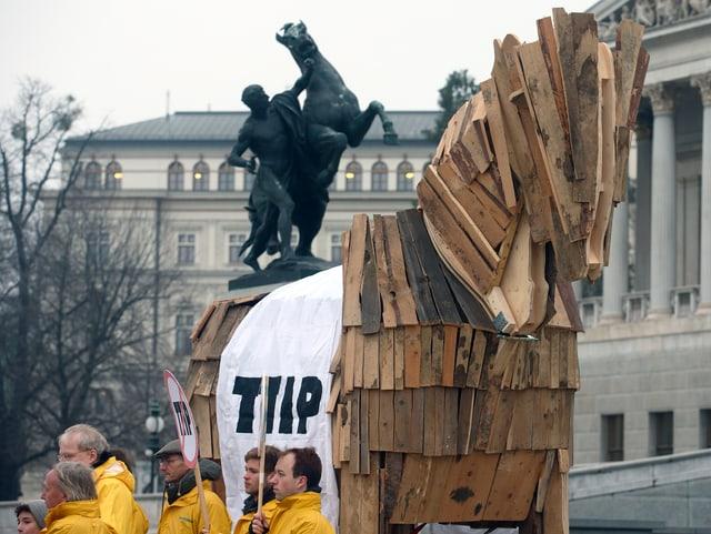 Demonstranten vor dem Wiener Parlament mit einem trojanischen Pferd und einem Transparent gegen TTIP.