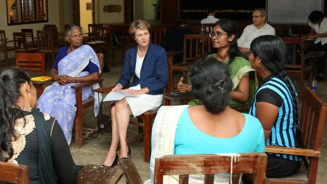 Sommaruga sitzt im Kreis mit Frauen und spricht mit ihnen.