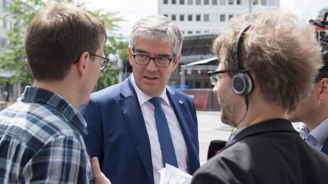 Der Politiker wird von zwei Journalisten interviewt.