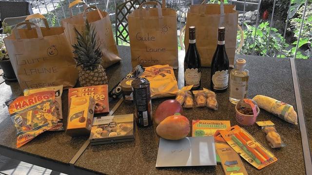 Vier Taschen voller Süssigkeiten, Wein und Früchten.