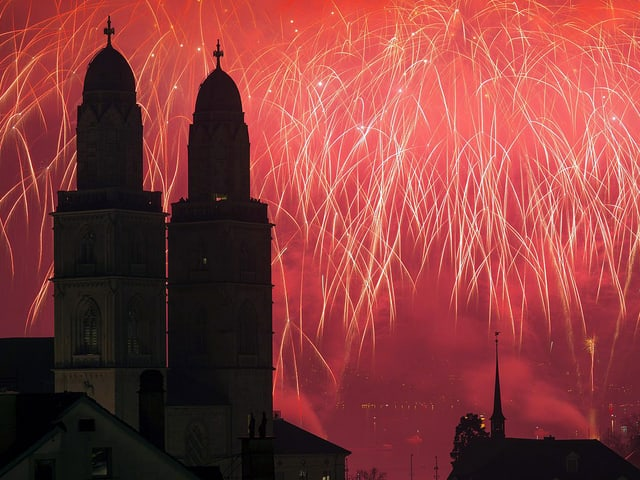 «Silvesterzauber» in Zürich. Hinter dem Grossmünster ist der Himmel rot erleuchtet.