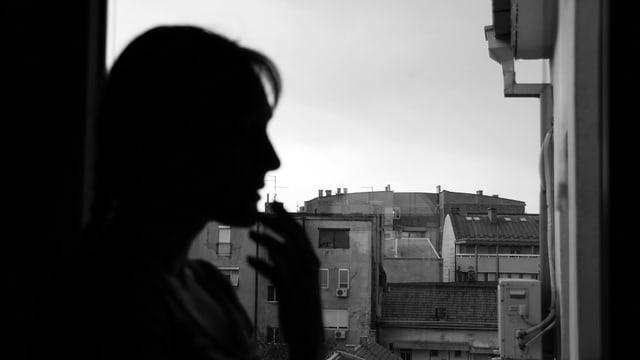 Silhouette einer Frau am Fenster, Häuser im Hintergrund