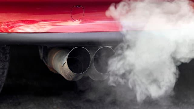 Ein Auspuff raucht an einem Auto.