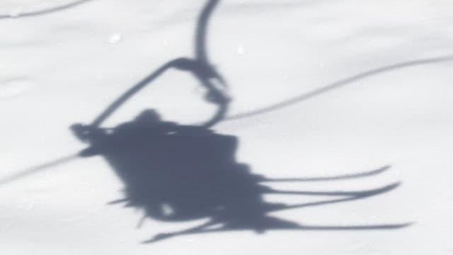 Schatten eines besetzten Sessellifts im Schnee