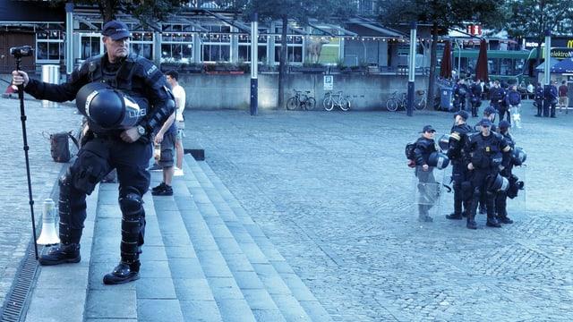Viele Polizistinnen und Polizisten auf dem Barfüsserplatz. Im Vordergrund steht einer mit einer Kamera auf einem Einbeinstativ.