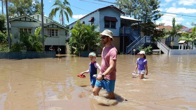 Ein Erwachsener und zwei Kinder schreiten bei Brisbane durch die Fluten.