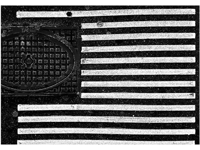 Ein Gulli und weisse Bodenstreifen für Blinde. Die Bildkomposition lässt den Boden wie die US-Flagge erscheinen.